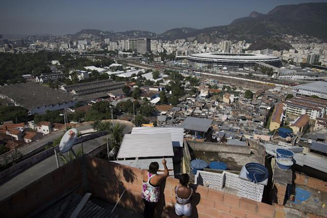 In this Wednesday, June 4, 2014 photo, women visit on a rooftop where they can see Maracana stadium from the Mangueira slum in Rio de Janeiro, Brazil. With tickets to the World Cup tournament expensive and hard to come by, the gulf between Mangueira and Maracana is almost impassable. (AP Photo/Leo Correa)