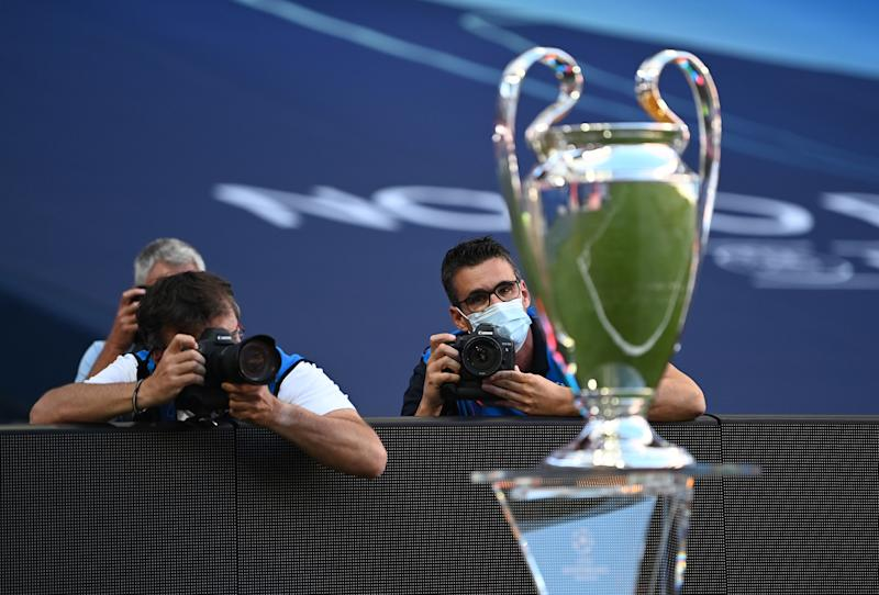 LISBON, PORTUGAL - AUGUST 23: Photographers are seen at work inside the stadium next to the Champions League Trophy prior to the UEFA Champions League Final match between Paris Saint-Germain and Bayern Munich at Estadio do Sport Lisboa e Benfica on August 23, 2020 in Lisbon, Portugal. (Photo by Michael Regan - UEFA/UEFA via Getty Images)