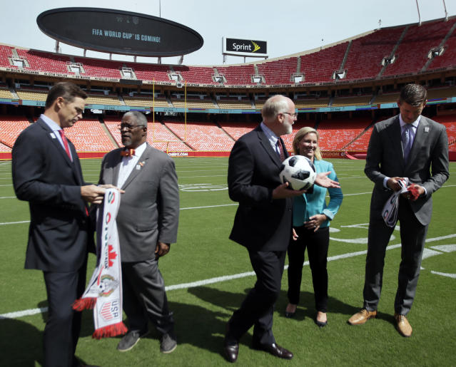 Kansas City Chiefs president Mark Donovan, left, Kansas City Missouri Mayor Sly James, second from left, Kansas City Kansas Mayor David Alvey, middle, Sports Commission president Kathy Nelson and Sporting Kansas City President and CEO Jake Reid, right, prepare to pose for a photograph following North America's successful bid to land the 2026 World Cup, at Arrowhead Stadium after in Kansas City, Mo., Wednesday, June 13, 2018. (AP Photo/Orlin Wagner)