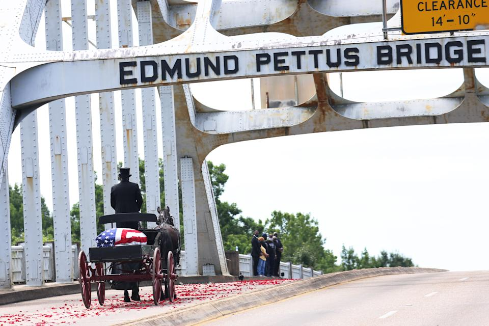 A horse-drawn carriage carrying the body of civil rights icon, former US Rep. John Lewis, crosses the Edmund Pettus Bridge as it prepares to pass members of his family on July 26, 2020 in Selma, Ala. (Photo by Michael M. Santiago/Getty Images)