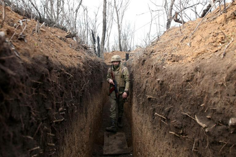 A Ukrainian serviceman walks in a trench on the frontline with Russia-backed separatists near the town of Krasnogorivka in the Donetsk region on April 23, 2021