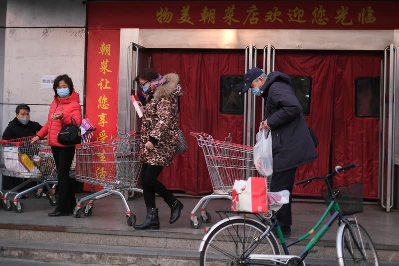 People wearing face masks walk out of a supermarket, as the country is hit by an outbreak of the new coronavirus, in Beijing