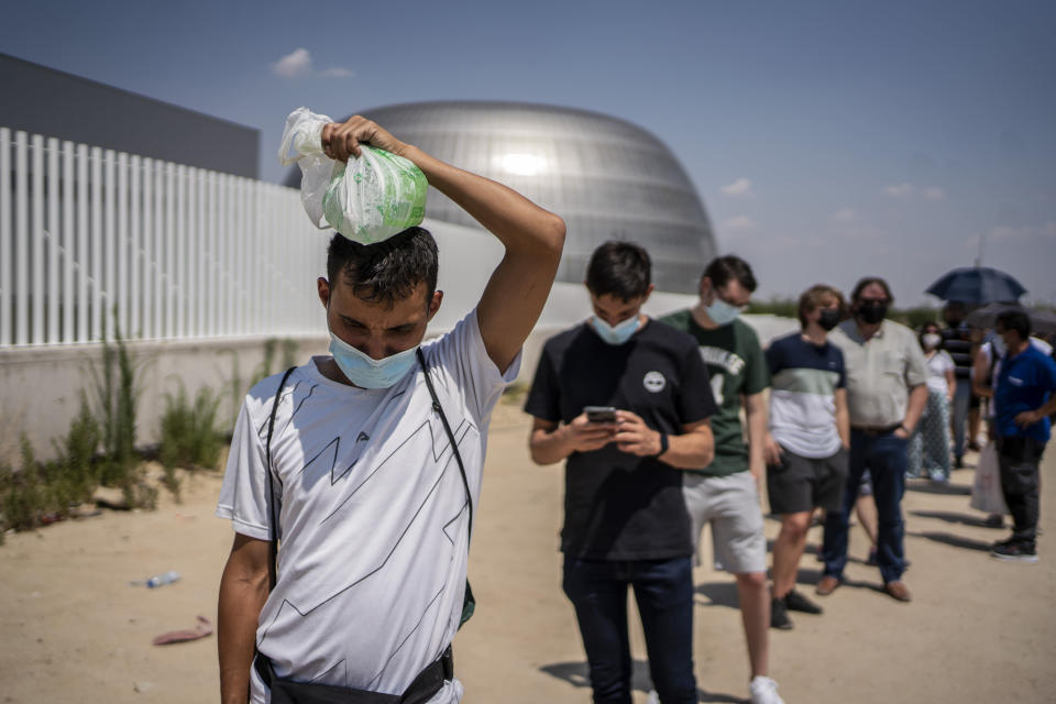 A man cools his head with an ice bag waiting to be vaccinated against Covid-19 at the Isabel Zendal Hospital in Madrid, Spain, Tuesday, July 20, 2021. Spain is trying to stamp out a new wave of COVID-19 among its youth thanks to a robust vaccination program that is widely supported. Spain like the rest of the European Union got off to a slow start to compared to the United States and Britain when the first vaccines were released. But it has quickly made up ground once deliveries by drug makers started flowing. (AP Photo/Olmo Calvo)