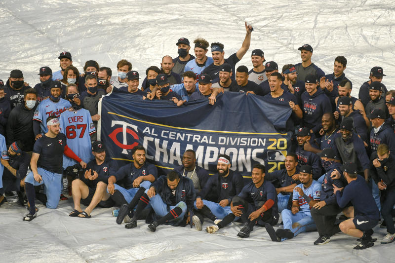 Members of the AL Central champions Minnesota Twins pose for a photo in the rain after their baseball game with the Cincinnati Reds, Sunday, Sept. 27, 2020, in Minneapolis. Twins clinched the AL Central championship with the Chicago White Sox's loss. The Reds won 5-3. (AP Photo/Craig Lassig)