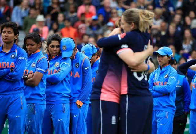 India's dejected players look on as England celebrate winning the women's cricket World Cup in 2017. The hosts completed a stunning fightback to triumph by nine runs. Seamer Anya Shrubsole finished with 6-46 – the best figures in a World Cup final – as India were bowled out for 219 with eight balls unused (John Walton/PA)