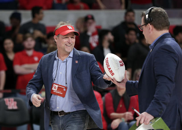FILE - In this Jan. 2, 2019, file photo, new Houston NCAA college football coach Dana Holgorsen get an autographed football to toss to fans during halftime of a basketball game between Houston and Tulsa, in Houston. The 2019 Most Likely to Succeed list ranks the new hires in FBS. (AP Photo/Michael Wyke, File)