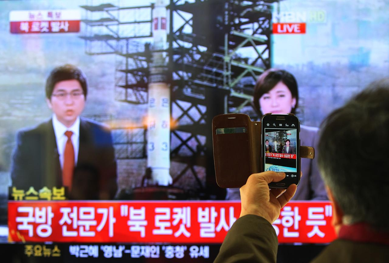 "South Korean man uses his smartphone to take a television screen reporting a news about North Korea's rocket launch at Seoul Railway Station in Seoul, South Korea, Wednesday, Dec. 12, 2012. North Korea fired a long-range rocket Wednesday in its second launch under its new leader, South Korean officials said, defying warnings from the U.N. and Washington only days before South Korean presidential elections. The letters on the screen read "" North Korea's rocket launch seems to be successful."" (AP Photo/Ahn Young-joon)"