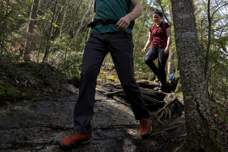 Kelsey Crosby, right, and Matt Hockemeyer descend the trail from Indian Head summit, Saturday, May 15, 2021, near St Huberts, N.Y. A free reservation system went online recently to control the growing number of visitors packing the parking lot and tramping on the trails through the private land of the Adirondack Mountain Reserve. The increasingly common requirements, in effect from Maui to Maine, offer a trade-off to visitors, sacrificing spontaneity and ease of access for benefits like guaranteed parking spots and more elbow room in the woods. (AP Photo/Julie Jacobson)