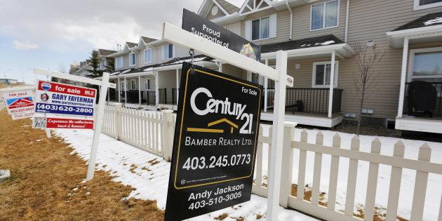 For sale signs line along a road where houses are for sale in Calgary, Alberta, April 7, 2015.