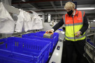 Britain's Prime Minister Boris Johnson loads produce into baskets during a visit to a tesco.com distribution centre in London, Wednesday, Nov. 11, 2020. (AP Photo/Kirsty Wigglesworth, pool)