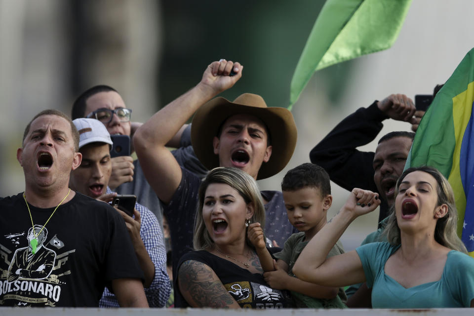 FILE - In this May 15, 2020 file photo, Sara Fernanda Giromini, known as Sara Winter, front center, demonstrates outside Planalto presidential palace in support for Brazilian President Jair Bolsonaro in Brasilia, Brazil. Giromini, the leader of a group that backs Bolsonaro, has been detained and prosecutors say she's suspected of raising funds for actions that could threaten the country's national security. (AP Photo/Eraldo Peres, File)