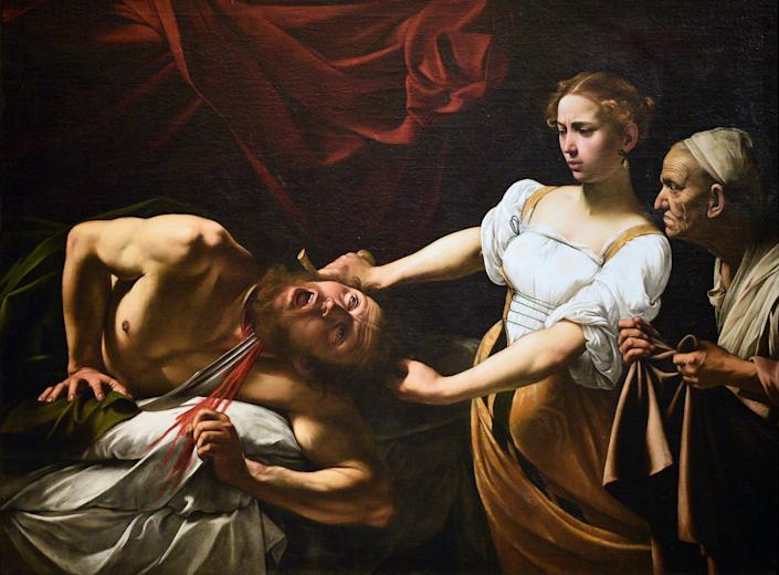 Judith tentatively slices off Holofernes' head.