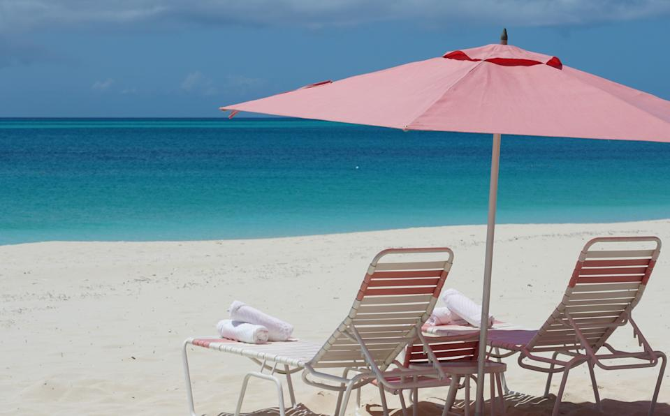 Beach loungers sport signature pink umbrellas at Ocean Club Resorts in Turks and Caicos Islands.