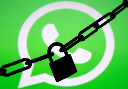 A photo illustration shows a chain and a padlock in front of a displayed Whatsapp logo