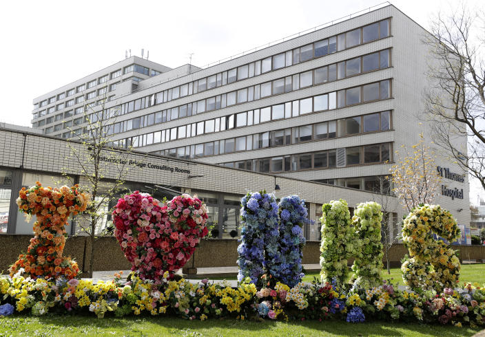 """Flowers arranged to read """"I love NHS"""" outside London's St Thomas' Hospital, where the PM is being treated for coronavirus. (AP)"""