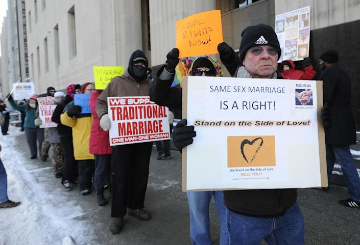 Protestors demonstrate outside Federal Courthouse before a trial that could overturn Michigan's ban on gay marriage in Detroit on Monday, March 3, 2014 in Detroit. Lisa Brown of Oakland County, the elected clerk of a Detroit-area county says she'll follow the orders of a judge when it comes to same-sex marriage, not Michigan's attorney general. Brown was asked about an email last fall from the attorney general's office, which warned county clerks not to issue marriage licenses to same-sex couples, even if a judge threw out the ban. Michigan voters banned gay marriage in 2004. In a lawsuit, Detroit-area nurses April DeBoer and Jayne Rowse say that violates the U.S. Constitution. (AP Photo/Detroit News, David Coates) DETROIT FREE PRESS OUT; HUFFINGTON POST OUT