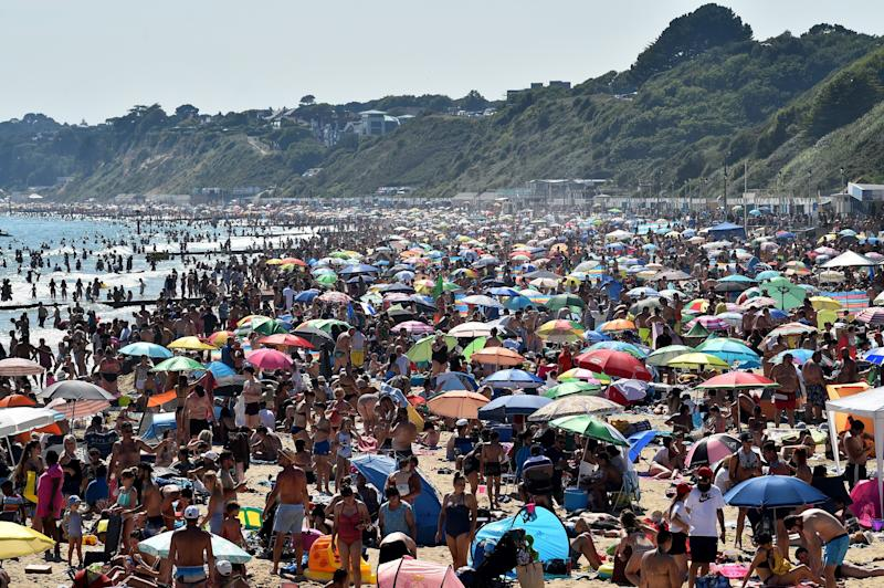 Beachgoers enjoy the sunshine as they sunbathe and swim on Bournemouth Beach in southern England on June 25. (Photo: GLYN KIRK via Getty Images)