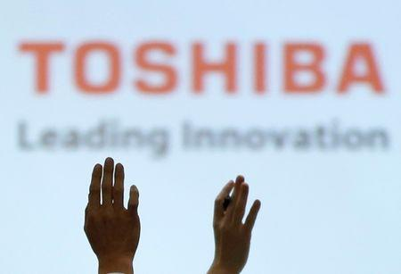 Reporters raise their hands for a question during a news conference by Toshiba Corp CEO Satoshi Tsunakawa and other senior sompany officials at the company's headquarters in Tokyo, Japan