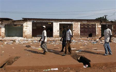 Men walk past looted stores belonging to Muslims in Combattant district in Bangui