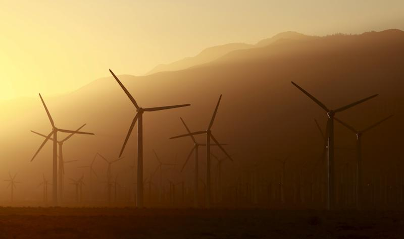 A windmill farm is seen in front of smoke from the Lake Fire in the San Bernardino National Forest, seen at sunset from Palm Springs, California June 18, 2015.  Some 500 firefighters backed by air tankers and bulldozers were battling the Lake Fire, which was raging across some 7,500 acres (3,000 hectares) and was just 5 percent contained, the San Bernardino County Fire Department said.  REUTERS/Sam Mircovich