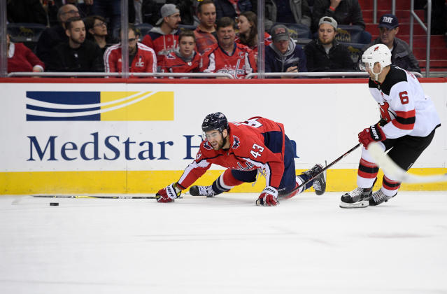 Washington Capitals right wing Tom Wilson (43) falls on the ice next to New Jersey Devils defenseman Andy Greene (6) during the second period of an NHL hockey game Saturday, April 7, 2018, in Washington. (AP Photo/Nick Wass)