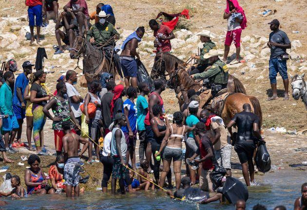 US border patrol agents interact with Haitian immigrants on the bank of the Rio Grande in Del Rio, Texas on Monday (Photo: John Moore via Getty Images)