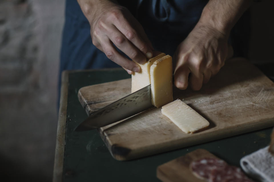 A person cutting into a block of cheese on a wood cutting board.