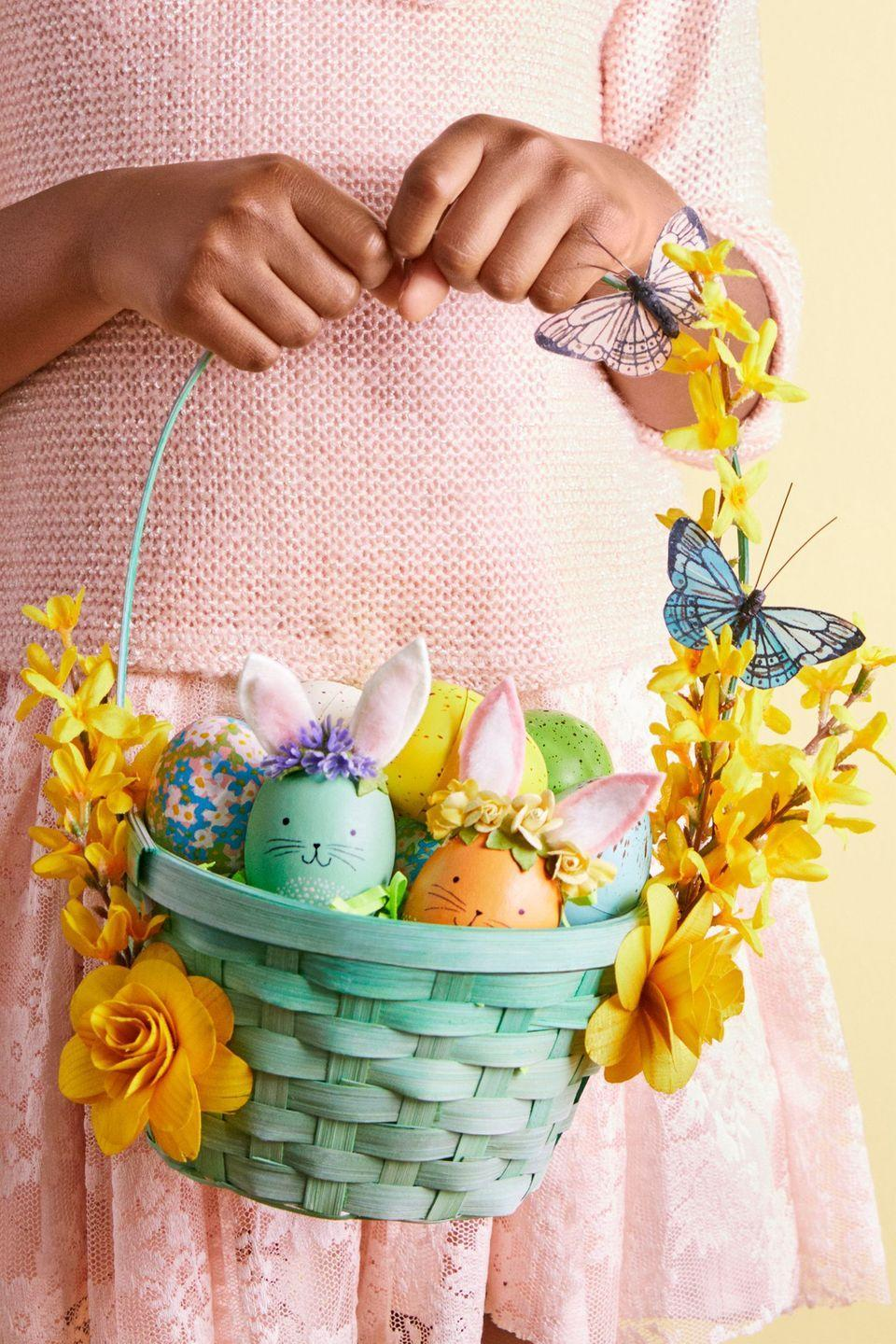 """<p>There are no better signs of warmer weather than beautiful blossoms and high-flying butterflies. Use the faux variety to embellish a bamboo basket, and fill with floral, speckled, and bunny-inspired eggs for added whimsy.</p><p><strong>Woodland Bunny:</strong> Decorate a painted egg with soft, furry ears and a floral crown. Paint a wooden egg, let dry, then add a spotted belly with white paint. Draw on a face. Use template to make ears from felt and faux-fur trim. Sandwich wire between ear pieces, then bend back the bottom 1/4 in. and use to glue in place. Glue small faux flowers around ears.</p><p><strong>Floral Egg:</strong> A dyed egg can be a blank canvas for a watercolor garden. Paint small X's with dots in the centers.</p><p><strong>Speckled Egg:</strong> Use a toothbrush to flick watered-down acrylic paint across (dry) spray-painted plastic eggs.</p><p><a class=""""link rapid-noclick-resp"""" href=""""https://www.amazon.com/BCP-25pcs-Blank-Plastic-Easter/dp/B01LWE37EP/?tag=syn-yahoo-20&ascsubtag=%5Bartid%7C10070.g.1751%5Bsrc%7Cyahoo-us"""" rel=""""nofollow noopener"""" target=""""_blank"""" data-ylk=""""slk:SHOP WHITE PLASTIC EGGS""""><strong>SHOP WHITE PLASTIC EGGS</strong> </a></p>"""