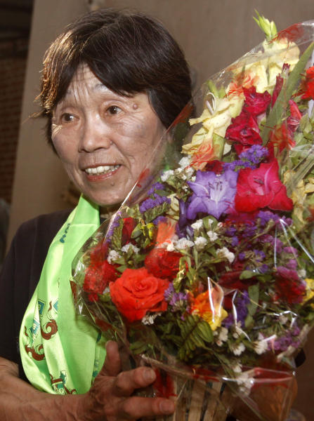 Oldest woman climber of Mount Everest, Tamae Watanabe of Japan, holds a bouquet of flowers after arriving in Katmandu, Nepal, Friday, May 25, 2012. Watanabe, 73, has made history by becoming the oldest woman to scale the world's highest mountain, Mount Everest, bettering a record, she herself set a decade ago. (AP Photo/Binod Joshi)