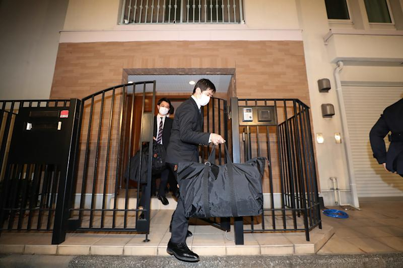 Japanese prosecutors carry bags as they leave the residence of former auto tycoon Carlos Ghosn on January 2, 2020, after Ghosn fled Japan to avoid a trial. - Former Nissan boss Carlos Ghosn, who fled to Lebanon to avoid a Japanese trial, had a second French passport, a source said on January 2, as authorities raided his Tokyo residence as part of a probe into the embarrassing security lapse. (Photo by STR / JIJI PRESS / AFP) / Japan OUT (Photo by STR/JIJI PRESS/AFP via Getty Images)