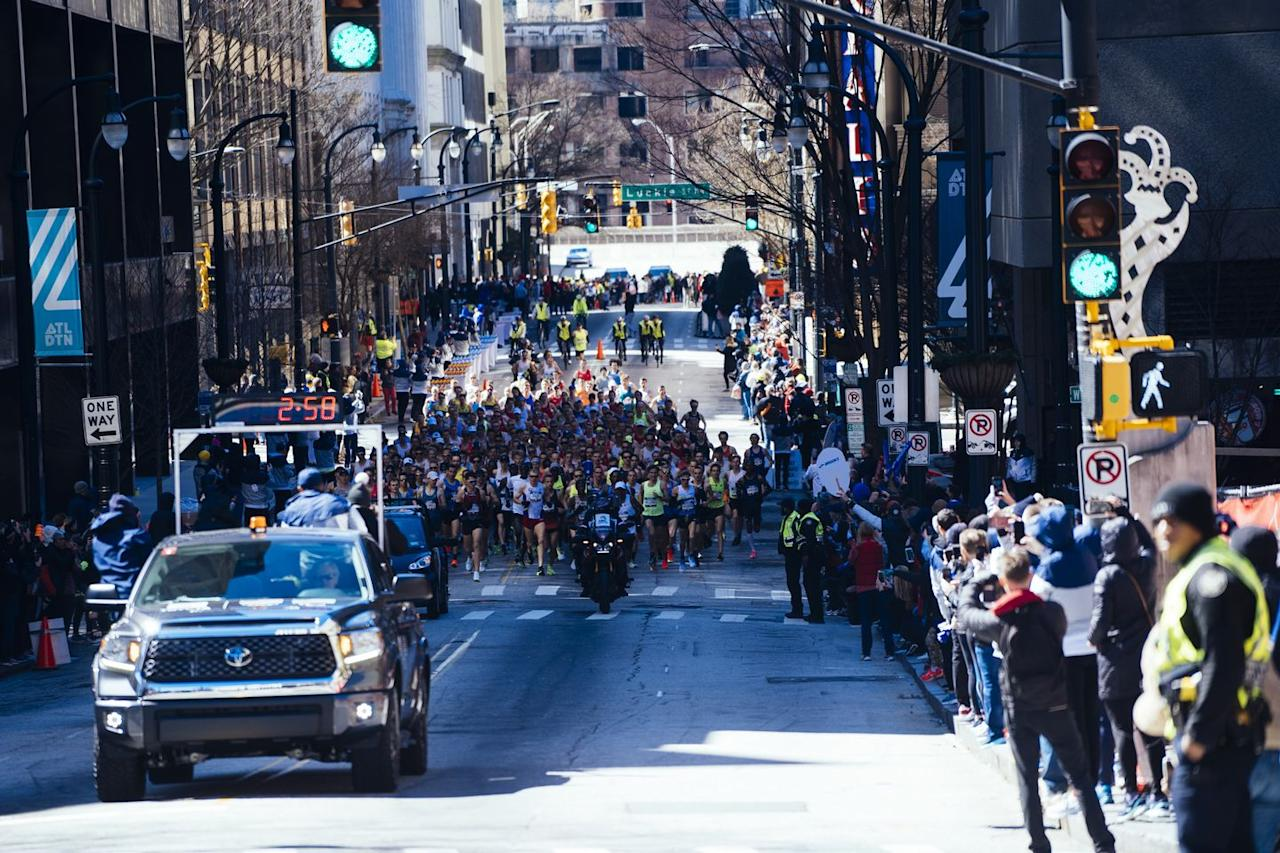 <p>Men's racers head uphill as a pack, just after the start. </p>