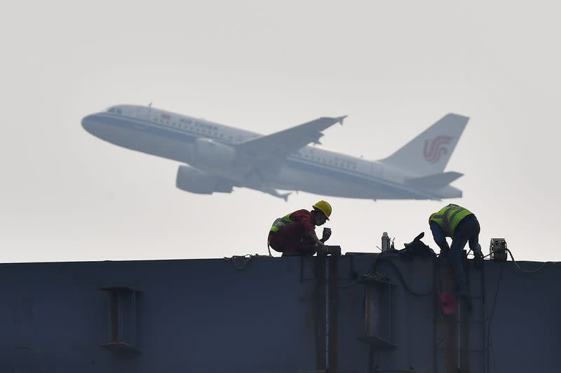 Air China plane flies past workers labouring at the construction site of an exhibition centre in Chengdu