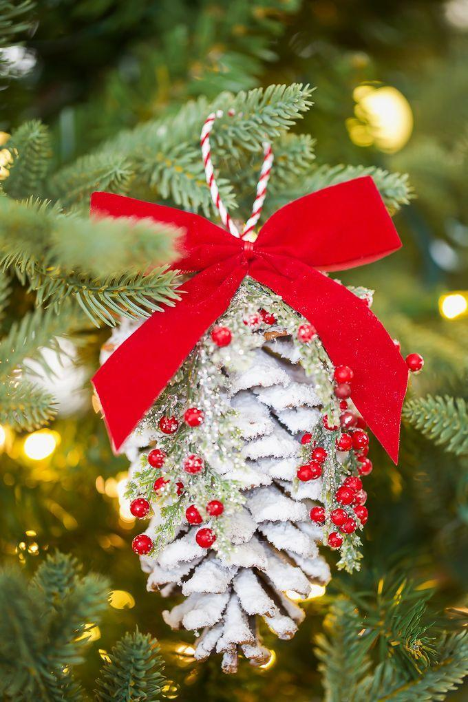 """<p>Make sure your tree looks like it belongs in the midst of a winter wonderland with flocked pinecones decorated with berries and big red bows. </p><p><em>Get the tutorial at <a href=""""https://apumpkinandaprincess.com/pine-cone-ornaments/"""" rel=""""nofollow noopener"""" target=""""_blank"""" data-ylk=""""slk:A Pumpkin and a Princess"""" class=""""link rapid-noclick-resp"""">A Pumpkin and a Princess</a>.</em></p><p><a class=""""link rapid-noclick-resp"""" href=""""https://www.amazon.com/Pacon-Spectra-Sparkling-Crystals-91830/dp/B007VHRAW6/?tag=syn-yahoo-20&ascsubtag=%5Bartid%7C10072.g.34443405%5Bsrc%7Cyahoo-us"""" rel=""""nofollow noopener"""" target=""""_blank"""" data-ylk=""""slk:SHOP WHITE GLITTER"""">SHOP WHITE GLITTER</a></p>"""