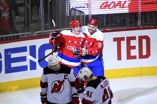 Washington Capitals center Nicklas Backstrom (19), of Sweden, celebrates his goal with center Evgeny Kuznetsov (92), of Russia, during the third period of an NHL hockey game, next to New Jersey Devils center Michael McLeod (41) and defenseman Andy Greene (6) Friday, March 8, 2019, in Washington. The Capitals won 3-0. (AP Photo/Nick Wass)