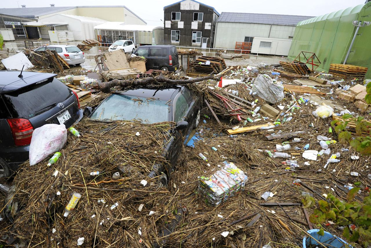 A parking lot is covered with trash from a flooded river due to heavy rain in Nagoya, central Japan Wednesday, Sept. 21, 2011. Heavy rains as a powerful typhoon approached caused floods and road damage in dozens of locations in Nagoya and several other cities, the Aichi prefectural (state) government said. (AP Photo/Kyodo News) JAPAN OUT, MANDATORY CREDIT, NO LICENSING IN CHINA, FRANCE, HONG KONG, JAPAN AND SOUTH KOREA