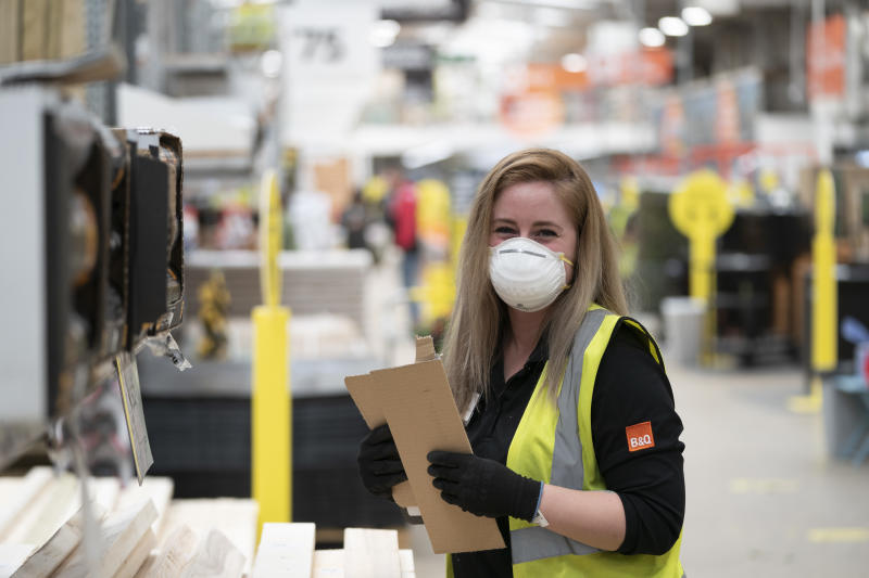 """LONDON, UK - MAY 15: Staff wear protective masks after the store adopted safe measures to protect both customers and staff at home improvement store B&Q in Chiswick as lockdown restrictions start to ease after 7 weeks on May 15, 2020 in London, England. The chain, part of the Kingfisher Group was classed as an essential retailer during the coronavirus lockdown. Shops were close in March but the chain was offering """"contactless"""" click and collect services. Now as restrictions are eased in the eighth of Lockdown, all 288 UK B&Q stores are now open. Following the example of supermarkets, B&Q is limiting the number of customers in store at any one time and has put strict social distancing measures in place. These include sanitiser stations for trolleys; safe queuing 2 metres apart before entering the store; 2 metre navigational markers on the floor and directional arrows to guide customers through the store; perspex screens at checkouts; and card and contactless payments only. The prime minister announced the general contours of a phased exit from the current lockdown, adopted nearly two months ago in an effort curb the spread of Covid-19. (Photo by Ming Yeung/Getty Images)"""