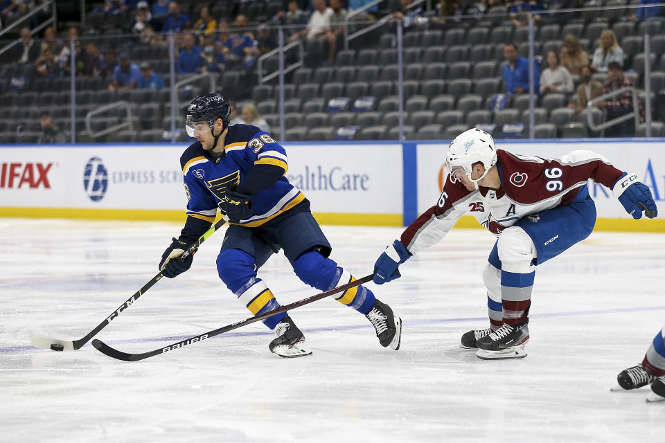 St. Louis Blues' Steven Santini (36) handles the puck while under pressure from Colorado Avalanche's Mikko Rantanen (96) during the second period in Game 3 of an NHL hockey Stanley Cup first-round playoff series Friday, May 21, 2021, in St. Louis. (AP Photo/Scott Kane)
