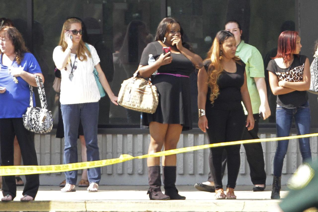 Parents and onlookers stand behind police tape after a vehicle crashed into a child care center in Winter Park, Florida April 9, 2014. Rescue officials say 12 people, including 11 children, were injured when a car crashed into a Goldenrod Road day care center. REUTERS/Stephen M. Dowell/Orlando Sentinel (UNITED STATES - Tags: DISASTER) NO SALES. NO ARCHIVES. FOR EDITORIAL USE ONLY. NOT FOR SALE FOR MARKETING OR ADVERTISING CAMPAIGNS. ATTENTION EDITORS - THIS PICTURE WAS PROVIDED BY A THIRD PARTY. REUTERS IS UNABLE TO INDEPENDENTLY VERIFY THE AUTHENTICITY, CONTENT, LOCATION OR DATE OF THIS IMAGE. THIS PICTURE IS DISTRIBUTED EXACTLY AS RECEIVED BY REUTERS, AS A SERVICE TO CLIENTS