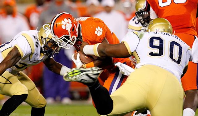 ATLANTA, GA - OCTOBER 29: D.J. Howard #22 of the Clemson Tigers is tackled by T.J. Barnes #90 and Rashaad Reid #28 of the Georgia Tech Yellow Jackets at Bobby Dodd Stadium on October 29, 2011 in Atlanta, Georgia. (Photo by Kevin C. Cox/Getty Images)