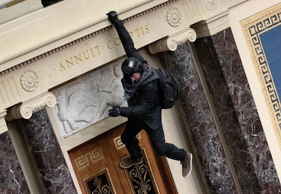 A protester supporting US President Donald Trump jumps from the public gallery to the floor of the Senate chamber at the US Capitol Building in Washington, DC.