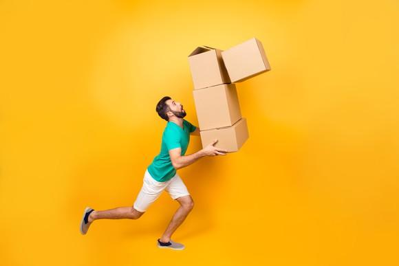 Man carrying boxes about to fall