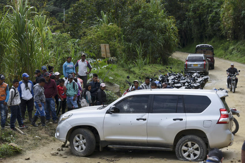 People gather around a car riddled by bullets on the road leading to Tacueyo, in southwest Colombia, Wednesday, Oct. 30, 2019. Five indigenous leaders of the Tacueyo reservation were killed late Tuesday when the two vehicles they were traveling in were ambushed by gunmen the government says are part of a dissident front of Revolutionary Armed Forces of Colombia. (AP Photo/Christian Escobar Mora)