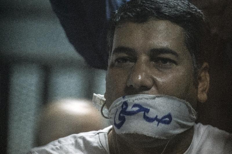 """Egyptian journalist Ibrahim al-Darawi has his mouth covered with a cloth gag reading in Arabic """"Journalist"""" as he and others stand trial in Cairo on June 2, 2015 (AFP Photo/Khaled Desouki)"""