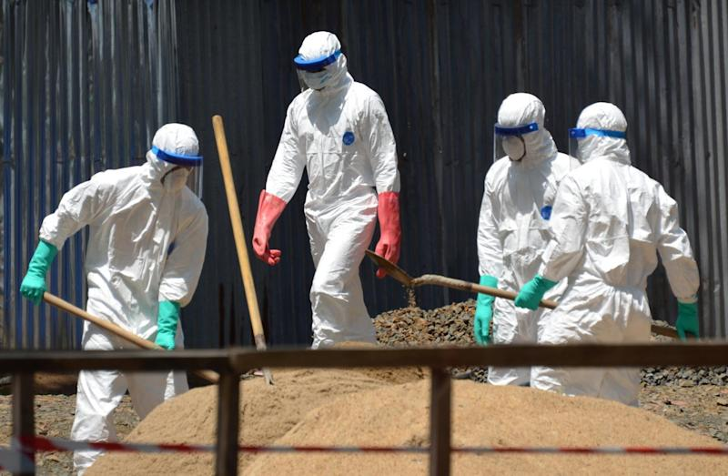 Health workers from the Liberian Red Cross wear protective gear as they shovel sand which will be used to absorb fluids emitted from the bodies of Ebola victims, in Monrovia on October 23, 2014 (AFP Photo/Zoom Dosso)