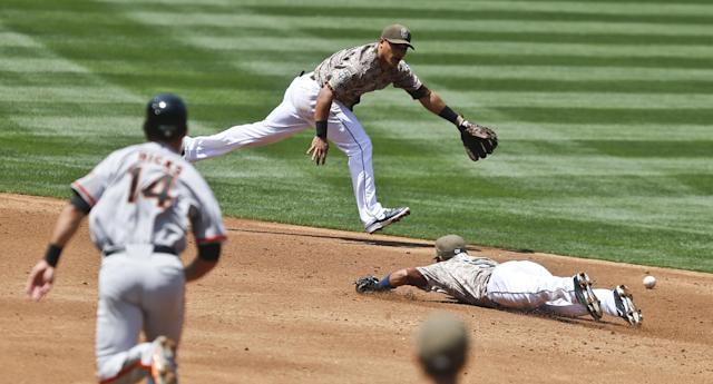 San Diego Padres second baseman Alexi Amarista, right, and shortstop Everth Cabrera, top, cannot reach a single by San Francisco Giants' Brandon Crawford as Giants baserunner Brandon Hicks (14) races around the bases to third in the second inning of a baseball game on Sunday, April 20, 2014, in San Diego. (AP Photo/Lenny Ignelzi)