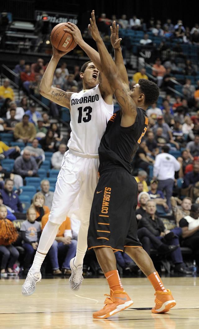 Colorado's Dustin Thomas (13) shoots against Oklahoma State's Le'Bryan Nash during the first half of an NCAA college basketball game on Saturday, Dec. 21, 2013, in Las Vegas. (AP Photo/David Becker)