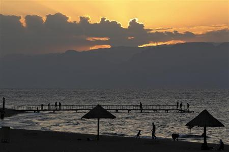 People are seen as the sun sets over a beach in the Aqaba Gulf on the Red Sea, south of Amman
