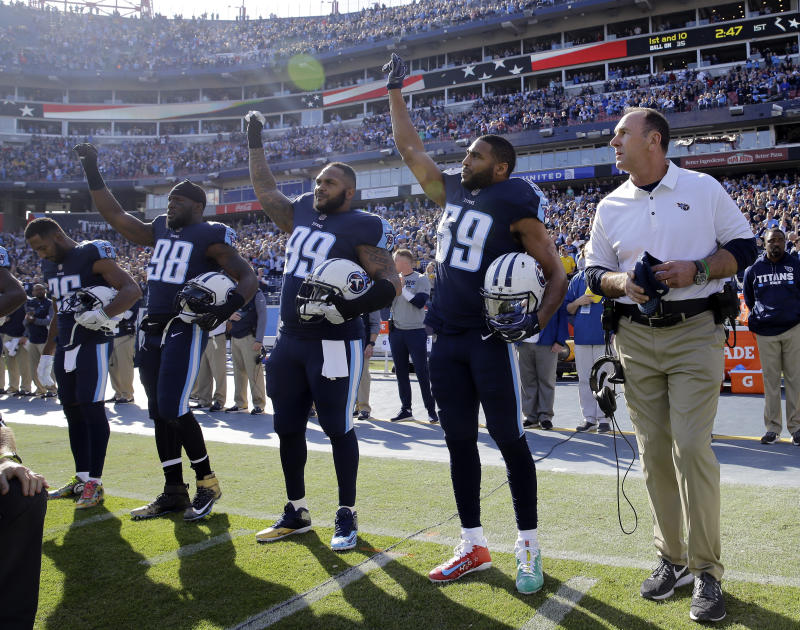 Tennessee Titans players Brian Orakpo (98), Jurrell Casey (99) and Wesley Woodyard (59) raise their hands after the national anthem last season. (AP)