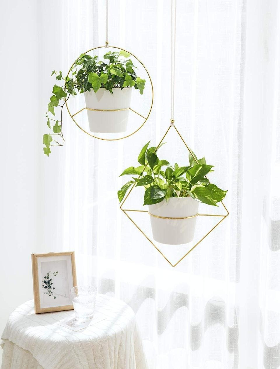 <p>Add a modern geometric flair with these <span>Mkono Modern Mid Century Boho Metal Hanging Planter, Set of 2 with Plastic Pots</span> ($31).</p>