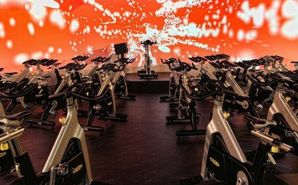 The spin studio has immersive graphics on a large projection screen, providing a distinct audio-visual atmosphere to enhance the workout. (photo from Virgin Active)